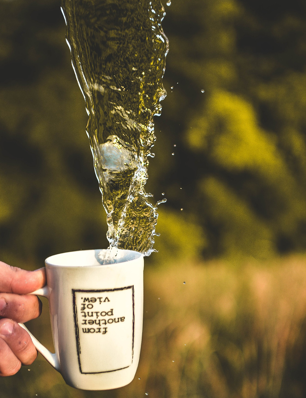 from another point of view on a written up side down on a coffee mug with water flowing out of it
