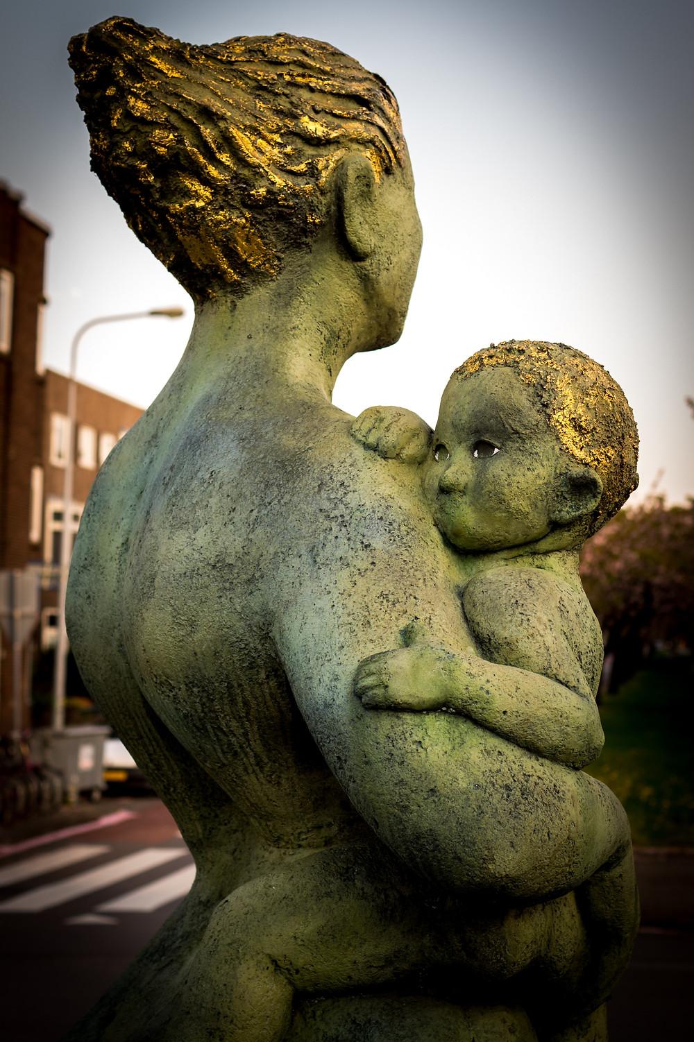 Estatua de mulher com criança ao colo