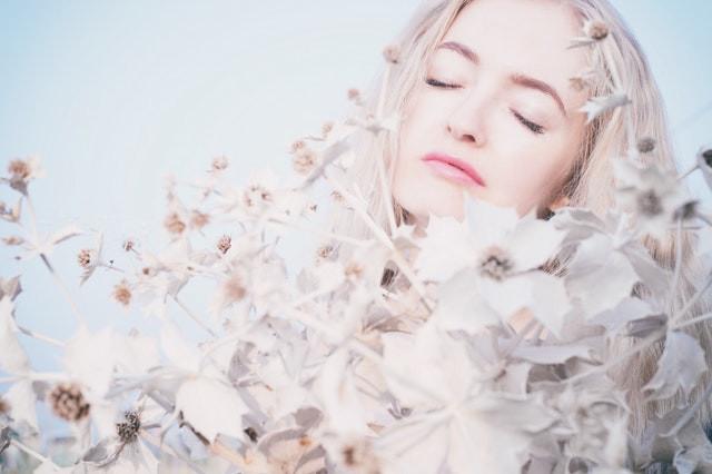 Mulher envolta em flores brancas