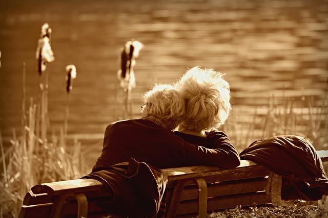 Casal sentados num banco em frente de um lago