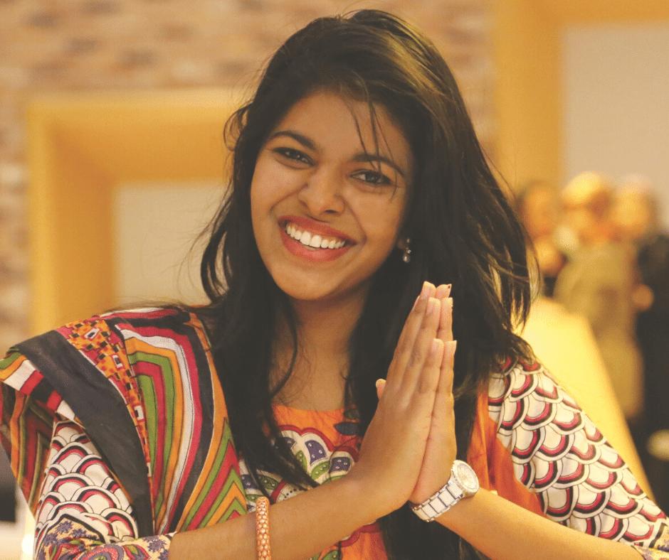 Mulher a sorrir com mãos em posição de Gratidão