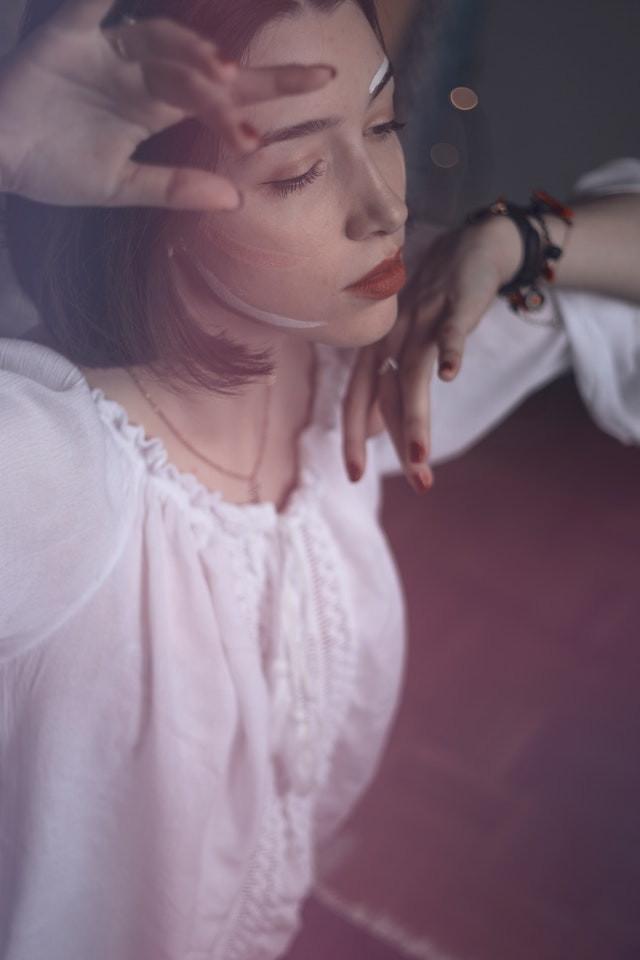 Rapariga a reflectir junto à janela.