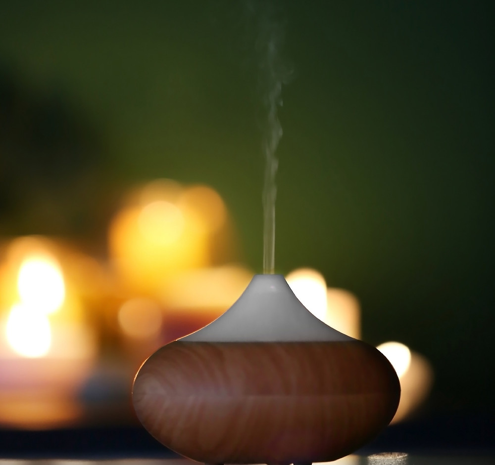 Essential oil difusor with lit candels in backround