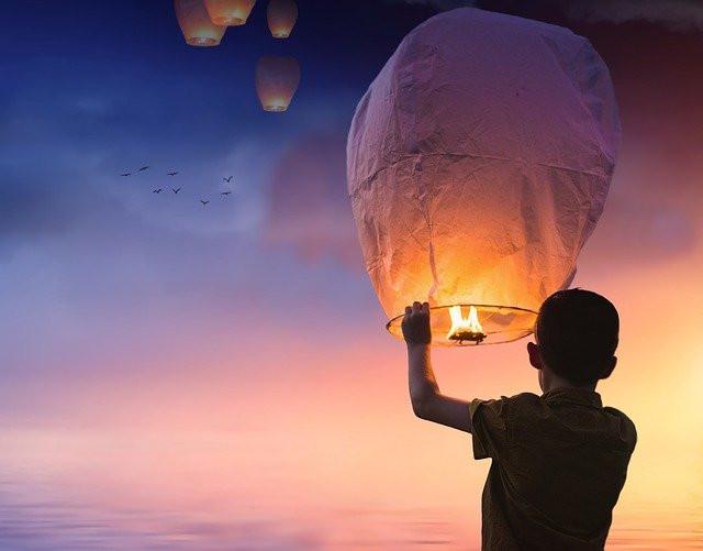 Rapaz a lagar um balão de ar, no pôr do sol