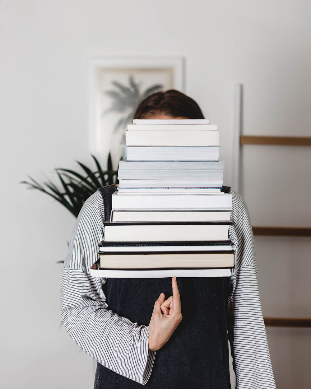 Girl Holding A Stack of Books