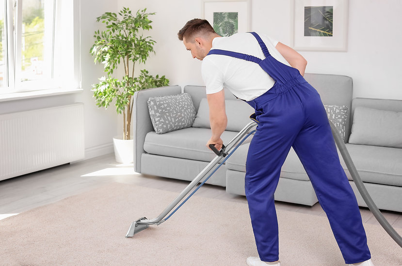 Male worker removing dirt from carpet wi