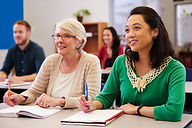 Two women sharing a desk at an adult edu