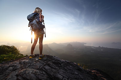 Young lady hiker standing with backpack