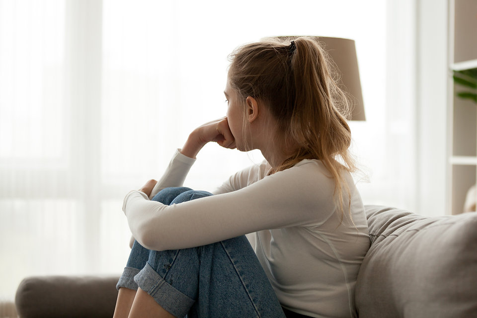 Young woman sitting, holding on to her legs and in deep tought.