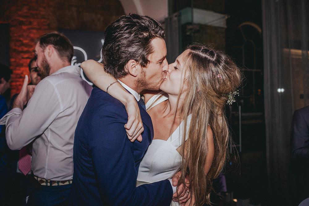 Emma and Ben enjoying a wedding kiss.