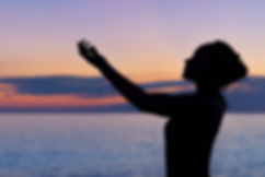 "alt=""woman with raised arms standing infront of the ocean with sunset behind her"""