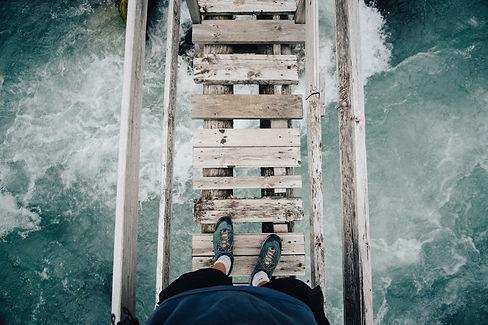 Mans feet on a bridge above water
