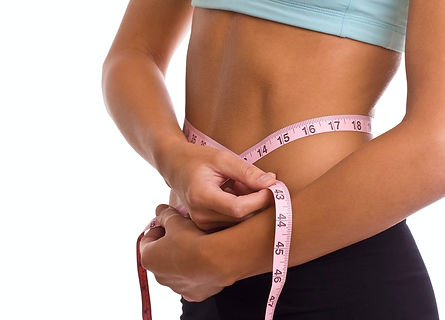 Woman holding measuring tape round stomach