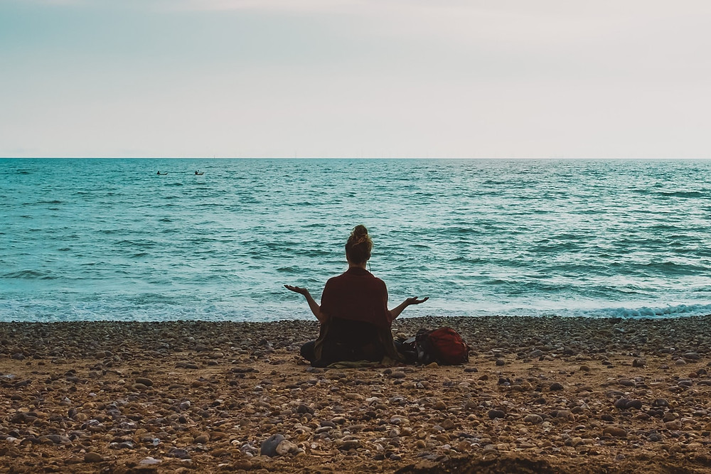 woman sitting on sand in front of the sea with hands out
