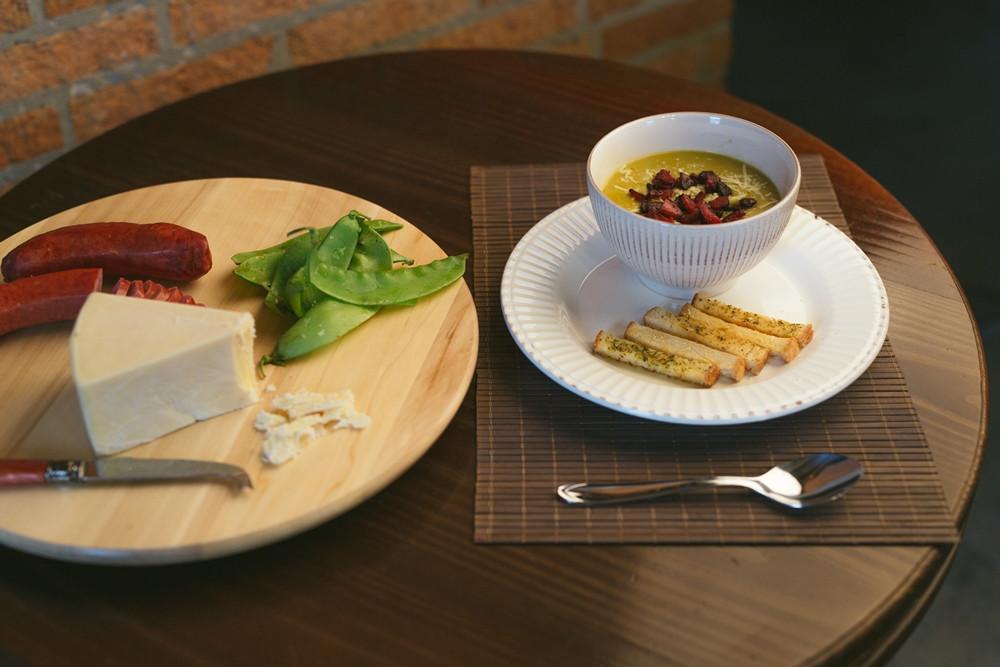 foto de uma sopa acompanhada de ervilha, linguiça e queijo sobre uma tábua de frio em cima de uma mesa