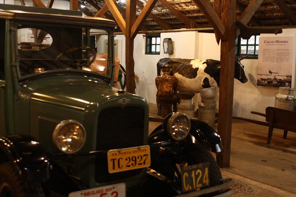 Imagem de um carro antigo e uma vaca decorativa em uma casa antiga