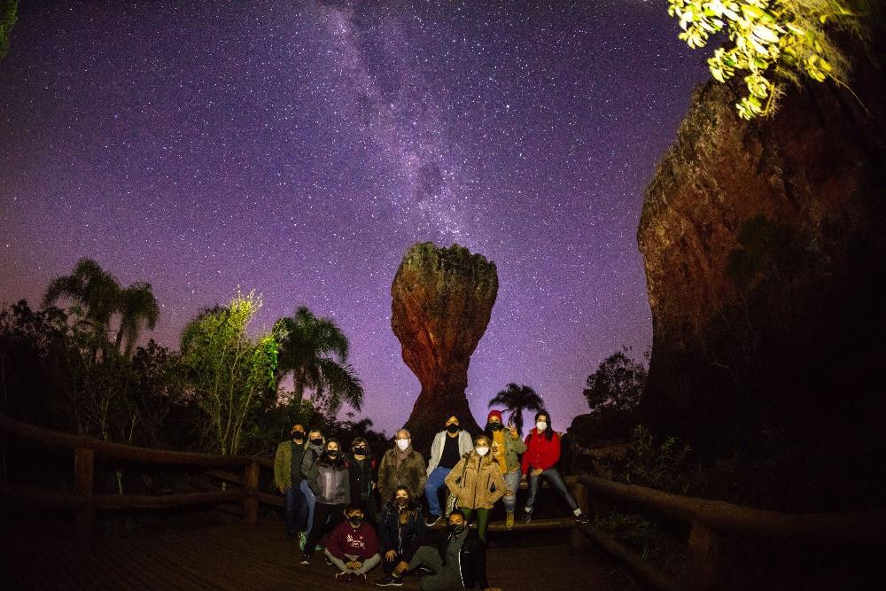 imagem do céu à noite no Parque de Vila Velha com a famosa taça ao fundo e pessoas em frente pousando para a foto