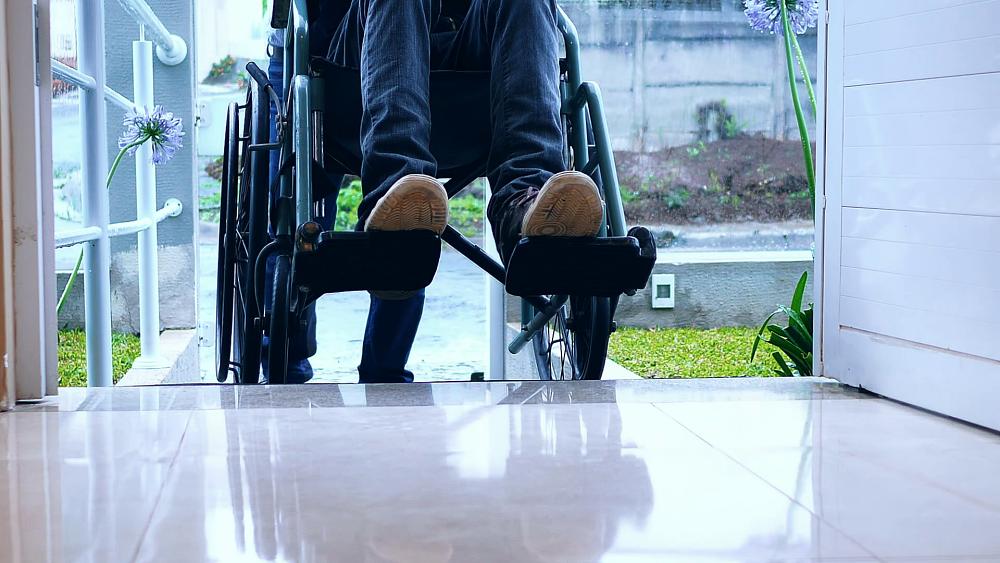 pessoa em uma cadeira de rodas entrando em uma clínica