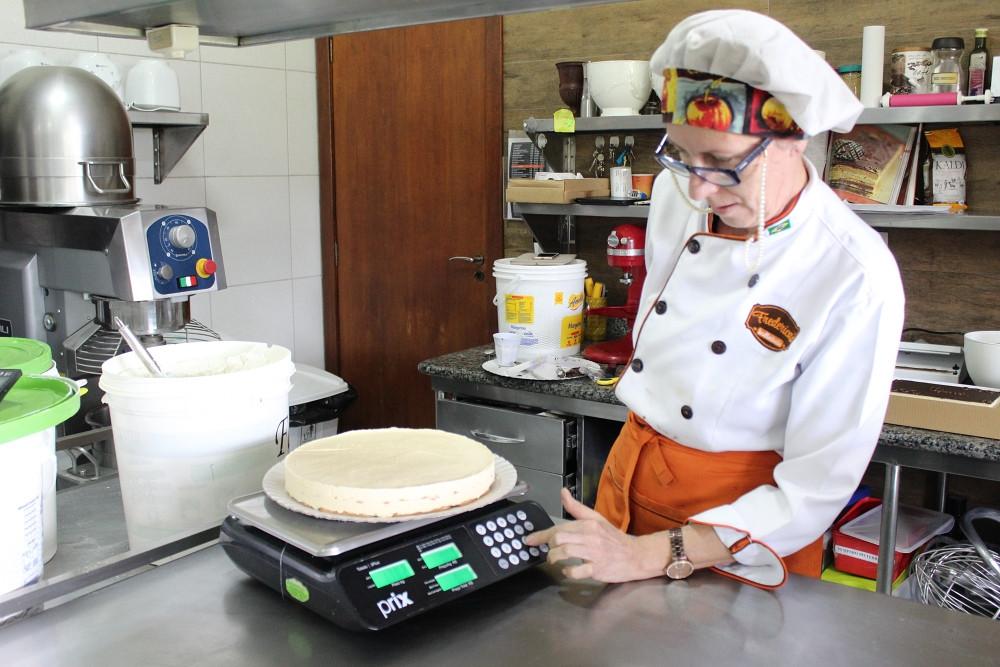 foto da Frederica conferindo o peso de uma torta na área de produção do Frederica's
