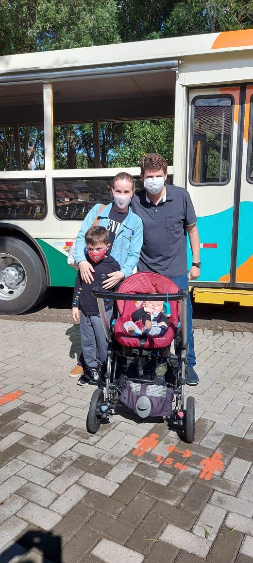 foto da família, sendo 2 adultos, 1 criança e um bebê num carrinho e atrás um ônibus do Parque