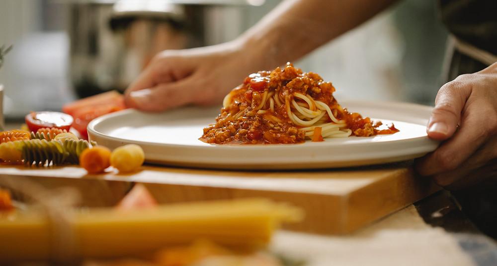 Imagem de um prato de macarrão sobre uma tábua de madeira