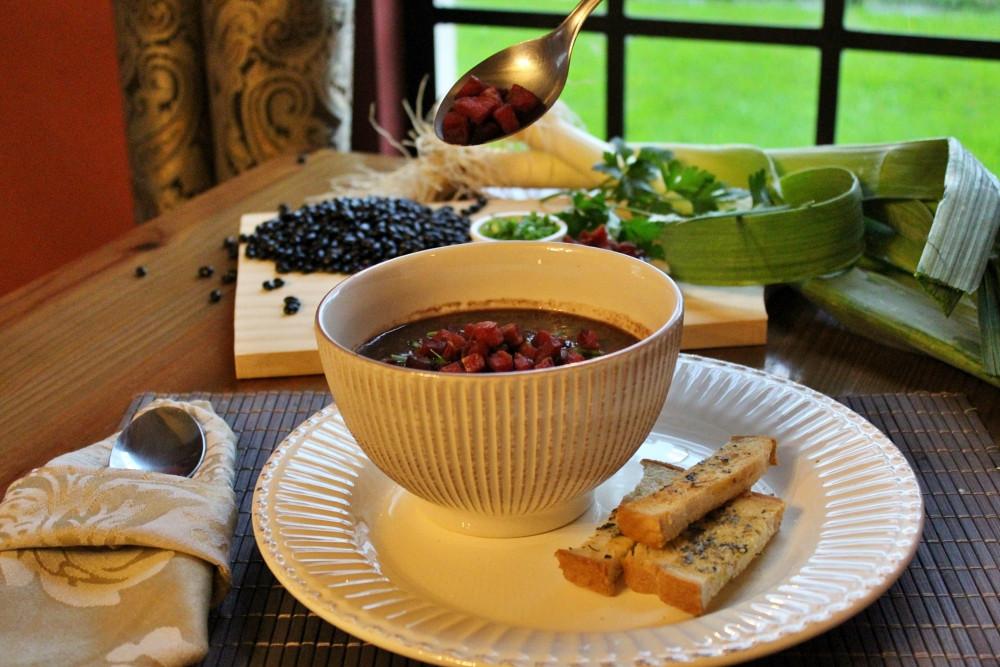 foto de uma sopa com o bacon sendo colocado e imagens de feijão e cheiros verdes ao fundo ilustrando o prato