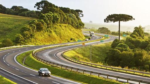 imagem de uma rodovia com poucos veículos e árvores ao redor