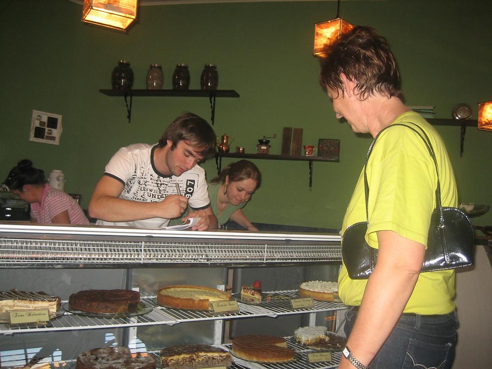 foto de uma pessoa escolhendo tortas em uma vitrine com 3 pessoas trás
