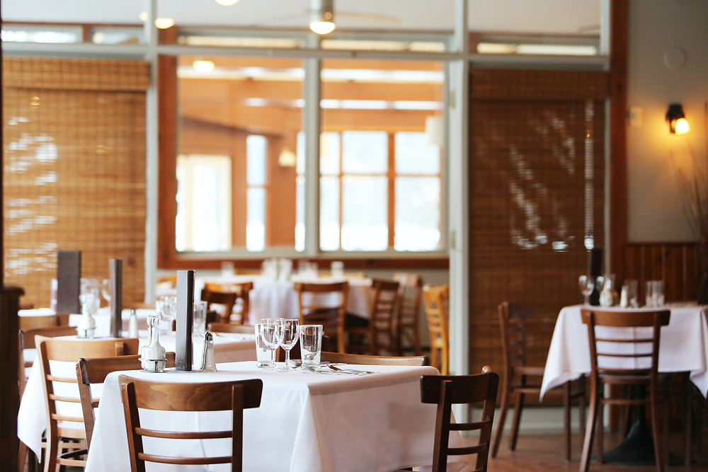 imagem de um restaurante com mesas e cadeiras vazias