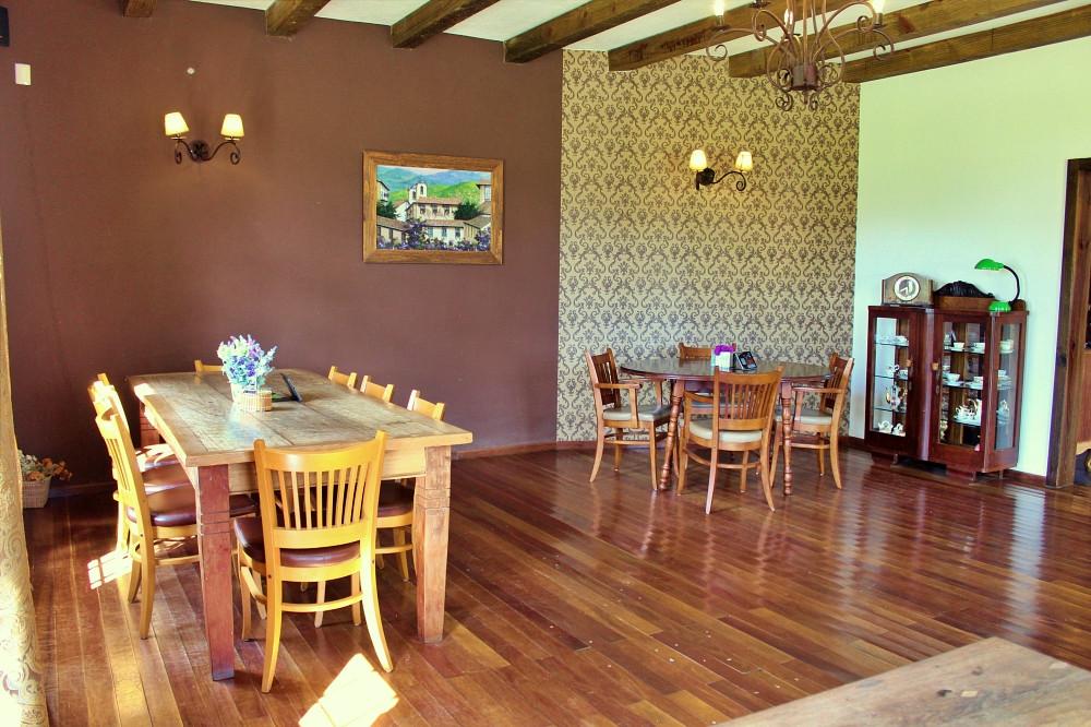 Imagem de uma grande salão com duas mesas ao fundo