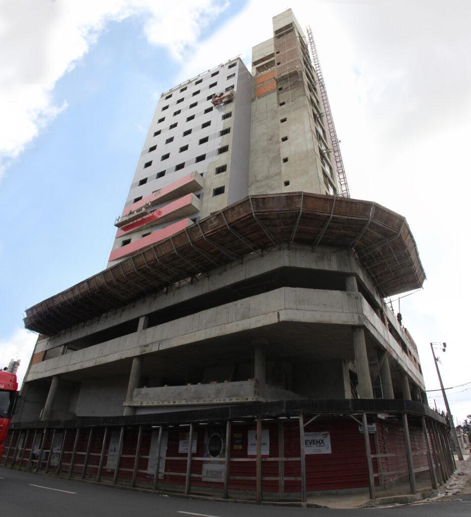 Imagem do hotel ramada em construção de baixo para cima com um céu azul com algumas nuvens