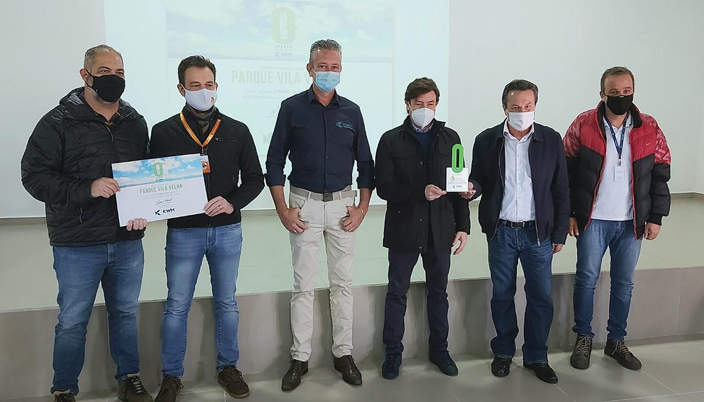 Foto dos gestores segurando uma certificação e prêmio