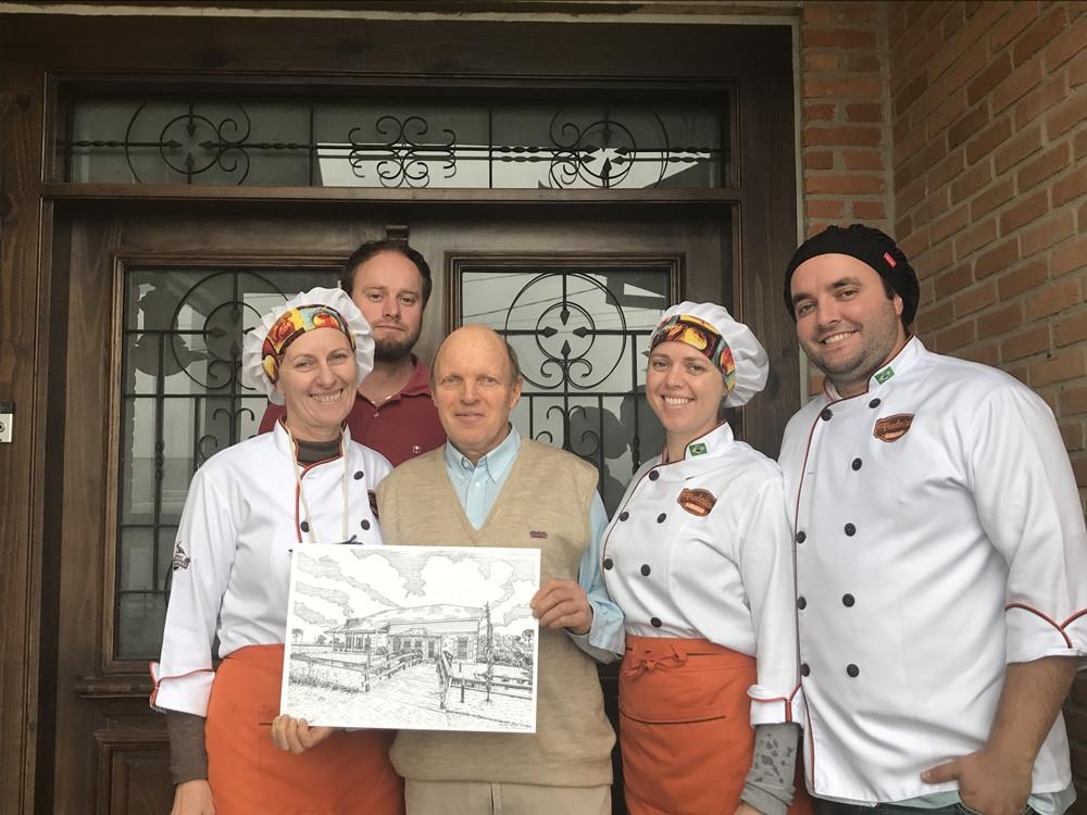 imagem da família junta ao artista segurando o Nanquim na entrada do Frederica's Koffiehuis