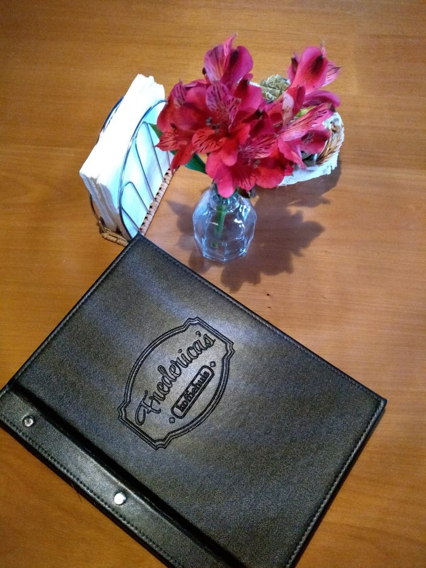 Foto do cardápio do Frederica's sobre uma mesa