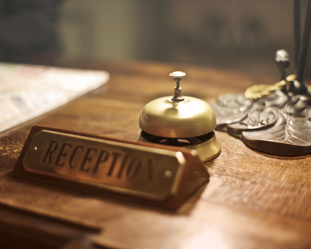 foto de uma recepção de hotel com a placa dourada escrita reception e uma campainha atrás