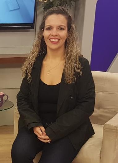foto da fonoaudióloga Tatiane Vieira sentada em uma poltrona marrom claro
