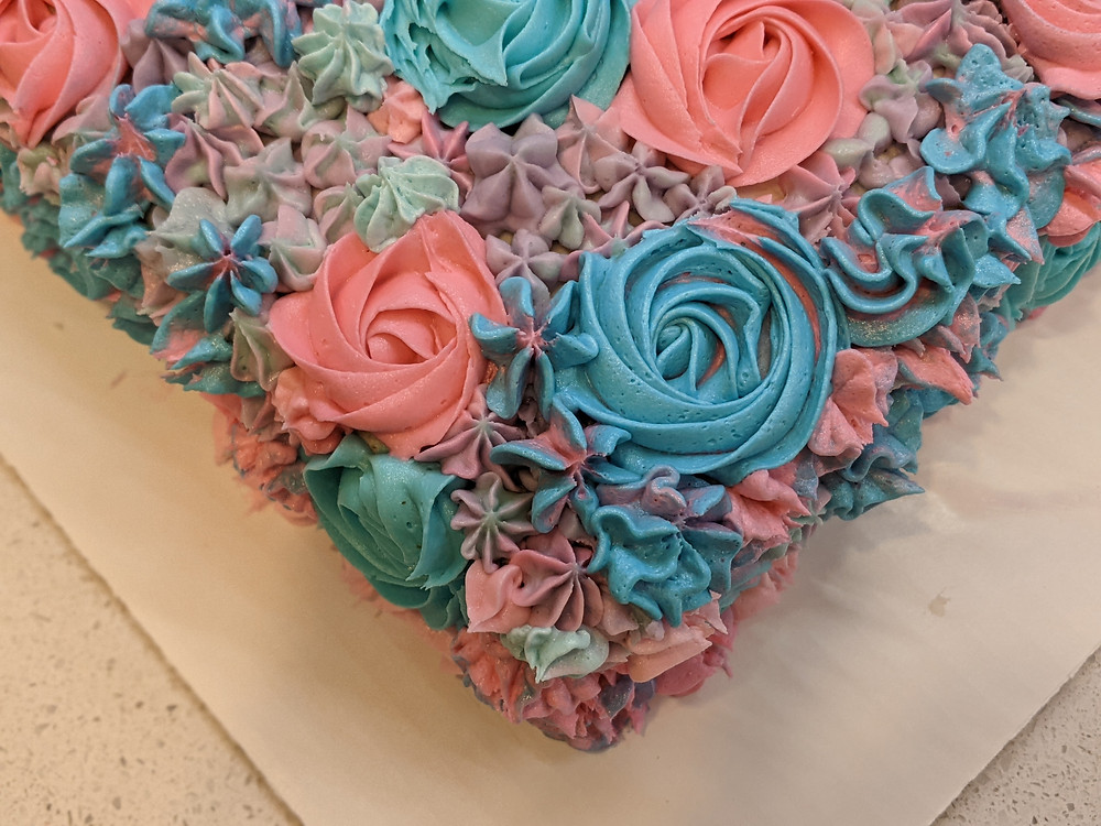 """A close of picture of the 9x13"""" cake corner showing detail of the blue, pink, and purple flowers."""