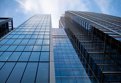 photo of a skyscraper against a blue sky, looking upwards