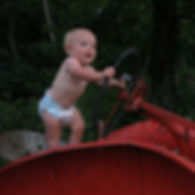 Baby driving antique tractor. Flower farm.