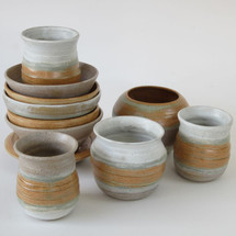 Collection of burnt orange ceramic vases and bowls by Sarah Burton Pottery
