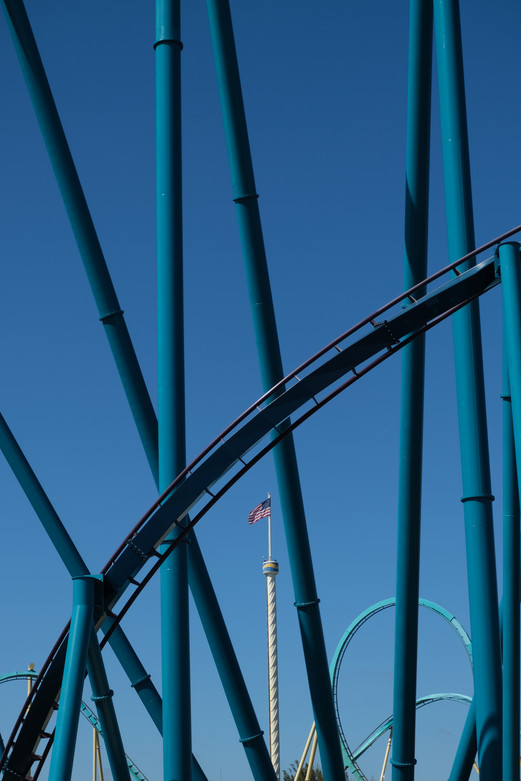 An American flag peeks out through rollercoaster tracks in Orlando, Florida.
