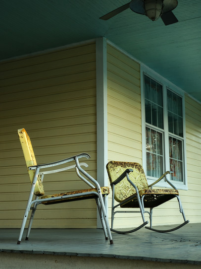 Two rusty chairs on a porch in Sanford, Florida.