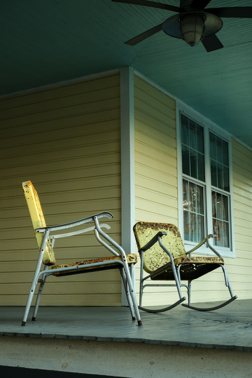 Two rusty chairs on a porch at sunset in DeLand, Florida.