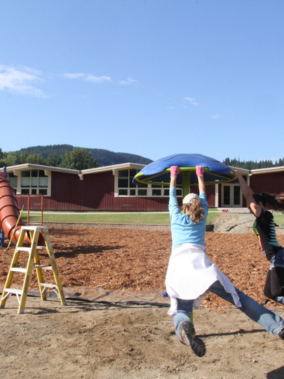 Kyran Kelso, Mazzie Hermes, Marcus Hermes and Sadie Peterson play on new equipment at the W.F. Morrison Elementary School in Libby, Montana, in 2014.