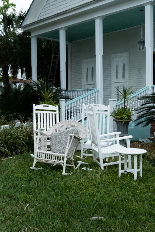 A cluster of wicker chairs perch outside a white house in Fernandina Beach, Florida.