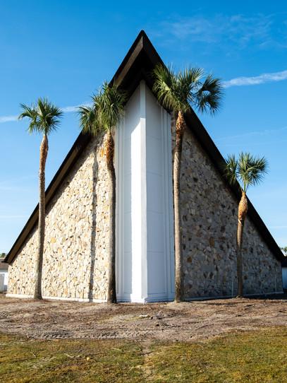Assymmetrical palm trees climb outside a symmetrical church in Orlando, Florida.