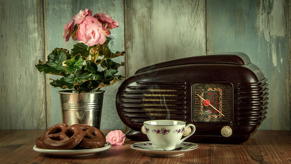a vintage radio with vas of roses and tea and biscuits