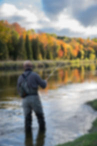 A man casts his fly rod into a river dur