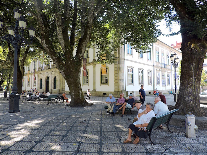 A group of seniors sit on a park bench in Viseu, Portugal.
