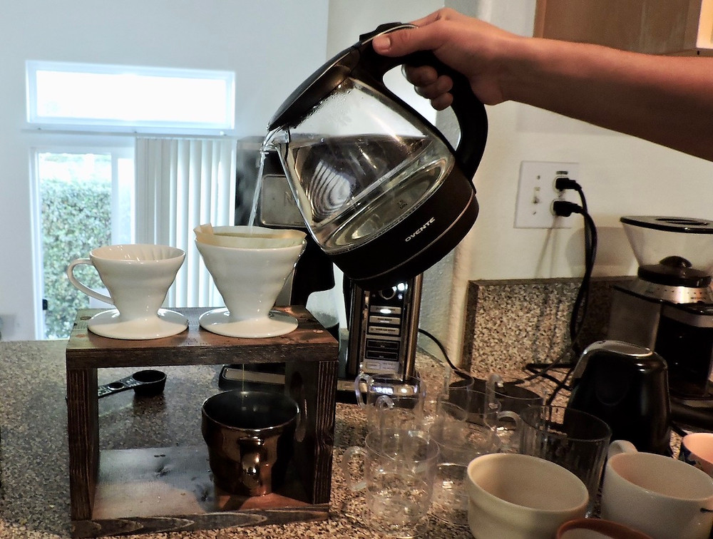 Guy pours water into pour over coffee containers
